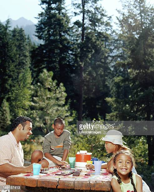 Father and mother sitting with son and daughter (6-11) at picnic
