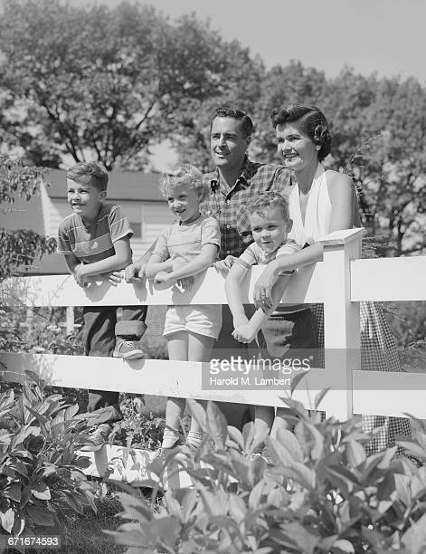 father and mother standing near fence with their children - {{ collectponotification.cta }} foto e immagini stock