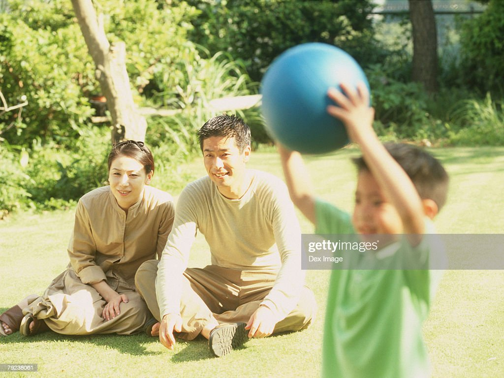 Father and mother watching son playing ball games : Stock Photo
