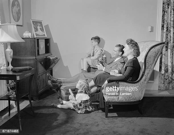 father and mother watching tv with their children - {{ collectponotification.cta }} foto e immagini stock