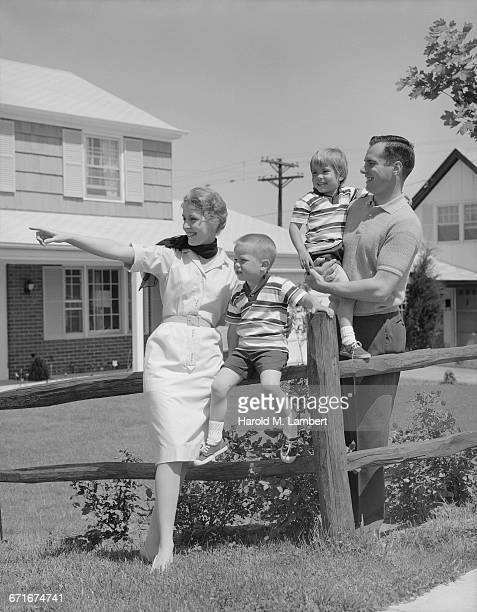 father and mother with kids standing in front yard by fence - {{ collectponotification.cta }} foto e immagini stock