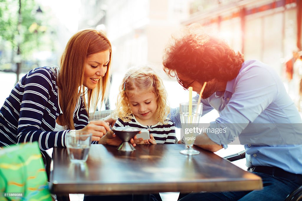 Father And Mother With Their Daughter in Cafe. : Stock Photo