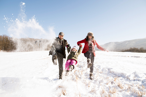 Father and mother with their daughter, playing in the snow. 865003508