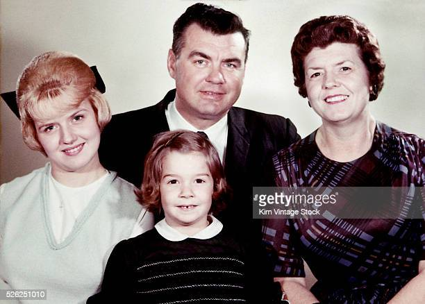 Father and mother with their two Baby Boomer daughters pose for a studio portrait in the mid-60s.