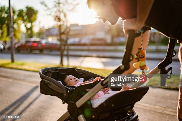 father and newborn baby walking on sunset - baby stroller stock pictures, royalty-free photos & images