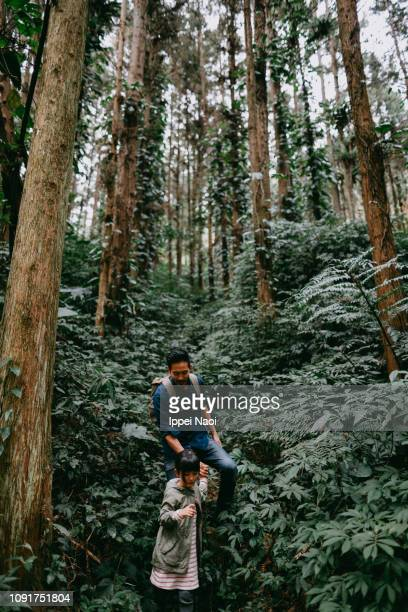 Father and preschool girl hiking in lush green rainforest