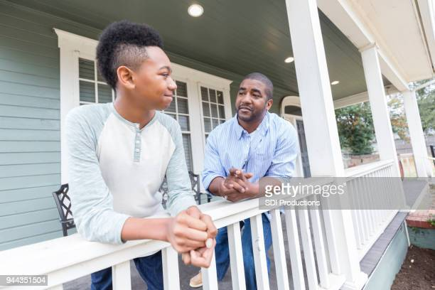 Father and preteen son enjoy time together on front porch