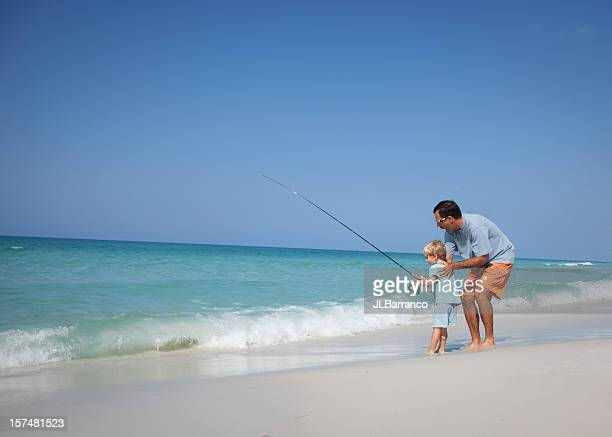 Father and small son fishing at the beach
