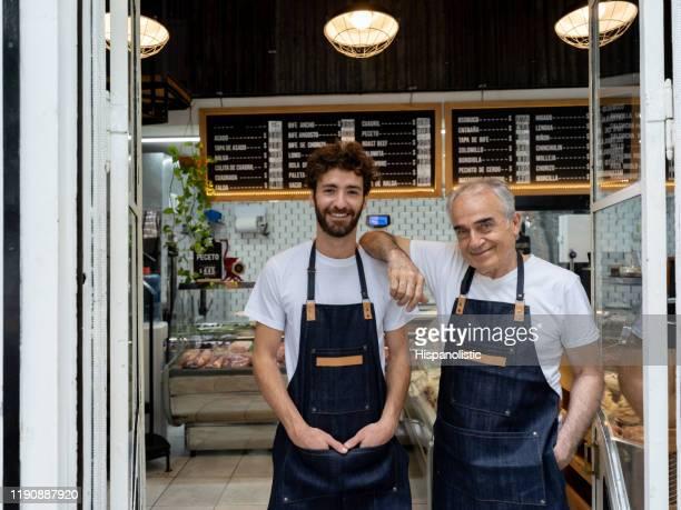 vader en dus eigenaren van een slager winkel staande bij de ingang glimlachend op de camera - pensioen thema stockfoto's en -beelden