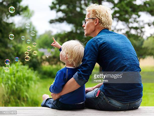 father and son admiring bubbles outdoors - denmark stock pictures, royalty-free photos & images