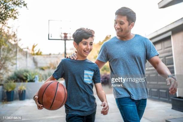 father and son after the basketball match on back yard - tee sports equipment stock pictures, royalty-free photos & images