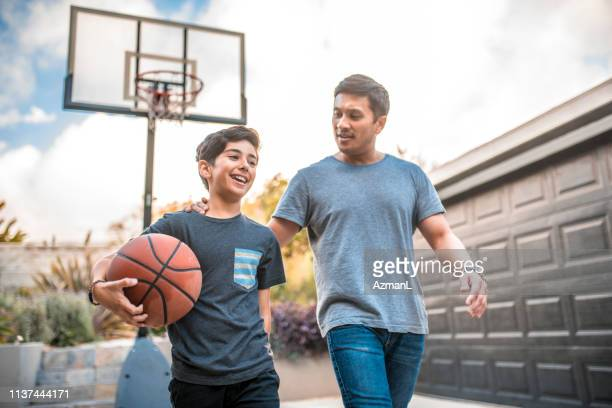 father and son after the basketball match on back yard - latin american and hispanic ethnicity stock pictures, royalty-free photos & images