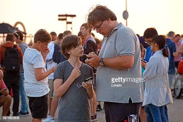 Father and son among Pokemon Go players on smartphones, Netherlands