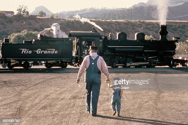 Father and Son Approaching Steam Locomotive