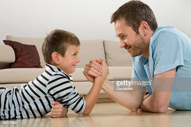 Father and son (4-5), arm wrestling, side view