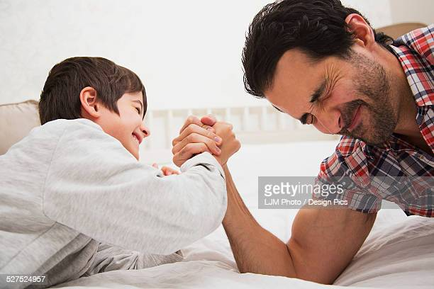 Father and son arm wrestling together on a bed