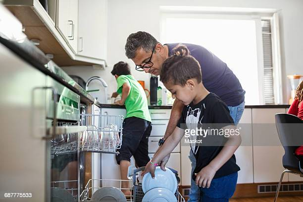 Father and son arranging plates in dishwasher at kitchen