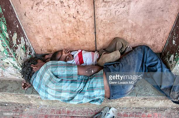 Father and son, asleep in Bangalore in doorway poverty all around INDIA