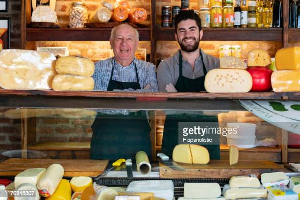 father and son at a family business delicatessen standing behind counter smiling at camera with arms crossed - bancarella foto e immagini stock