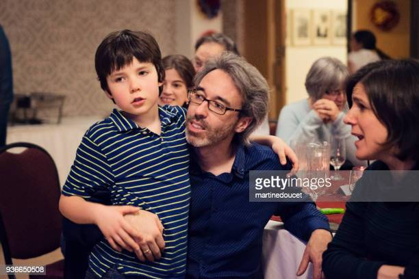 "father and son at a table in big family celebration dinner. - ""martine doucet"" or martinedoucet stock pictures, royalty-free photos & images"