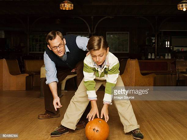 Father and son at bowling alley