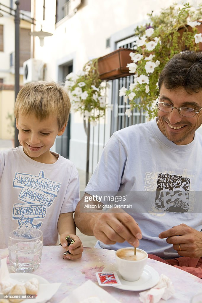 Father and son (4-5) at cafe with espresso : Foto stock
