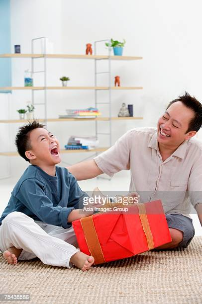 Father and son at home, boy opening gift, looking up