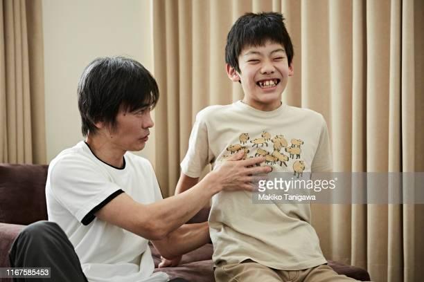 father and son at home - makiko tanigawa ストックフォトと画像
