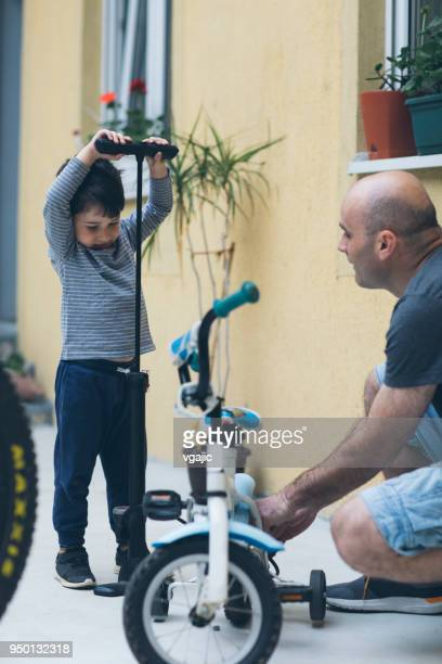father and son at home - air pump stock photos and pictures