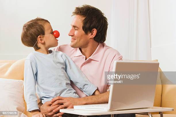 father and son (4-5) at laptop, boy wearing clown nose - clown's nose stock photos and pictures