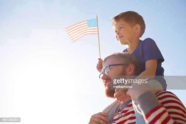 father and son at parade - independence day stock pictures, royalty-free photos & images