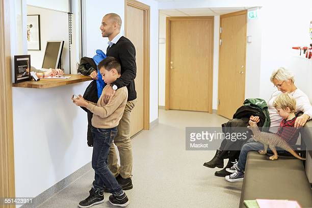 Father and son at reception counter while family waiting on bench at orthopedic clinic