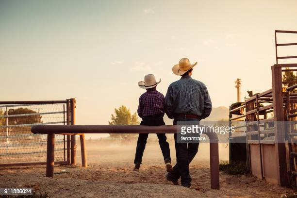 father and son at rodeo arena - cowboy hat stock pictures, royalty-free photos & images