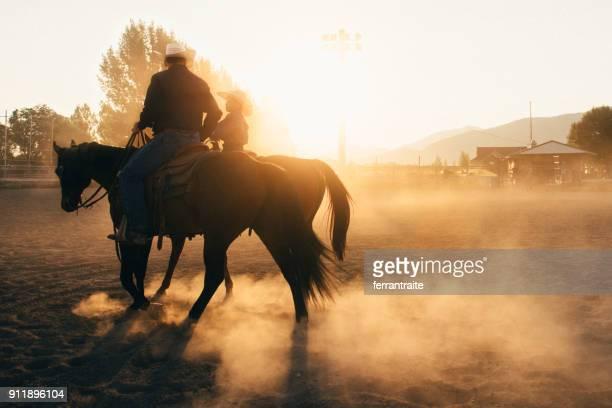 vader en zoon op rodeo arena - paard paardachtigen stockfoto's en -beelden