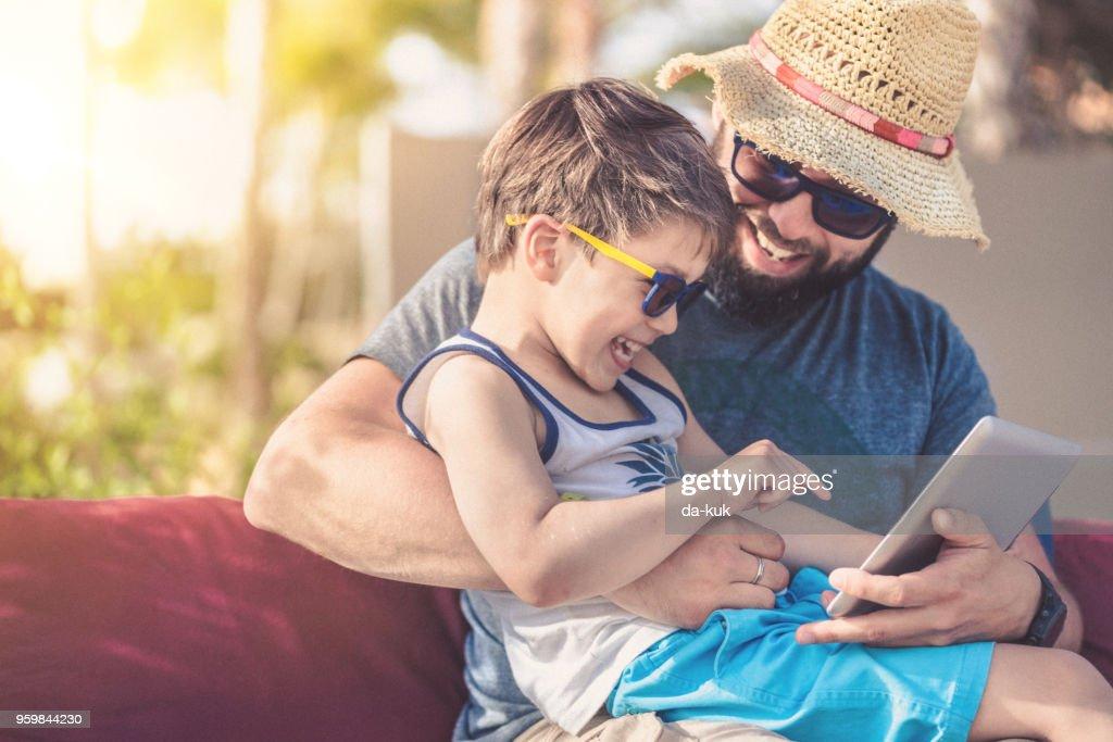 Vater und Sohn bei Sonnenuntergang mit digital-Tablette im Urlaub : Stock-Foto