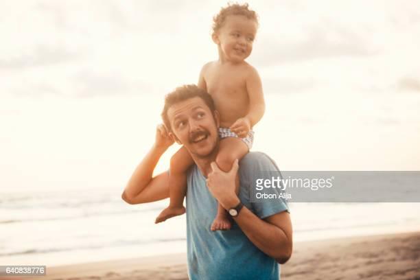 father and son at the beach - mexican and white baby stock photos and pictures