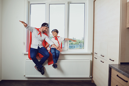 Father and son at the window in the room 972155664