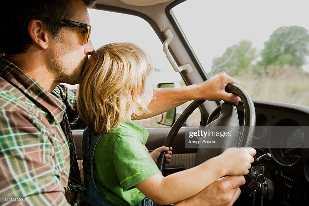 Father and son at wheel of a car : Stock Photo