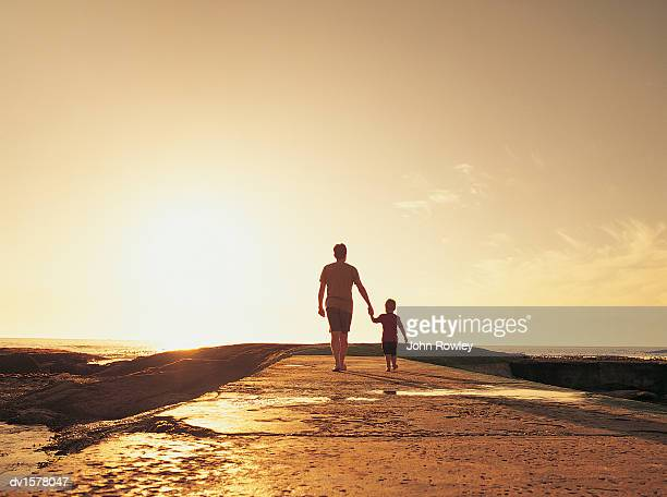 Father and Son Backlit by a Glowing Sun as They Walk Hand-in-Hand on a Pier Towards the Sea, South Africa