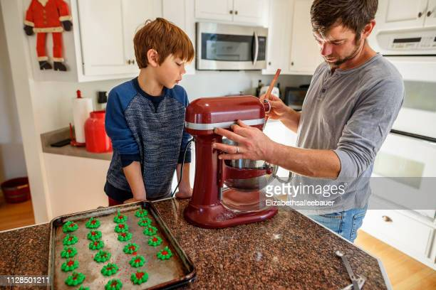 father and son baking cookies - electric mixer stock pictures, royalty-free photos & images