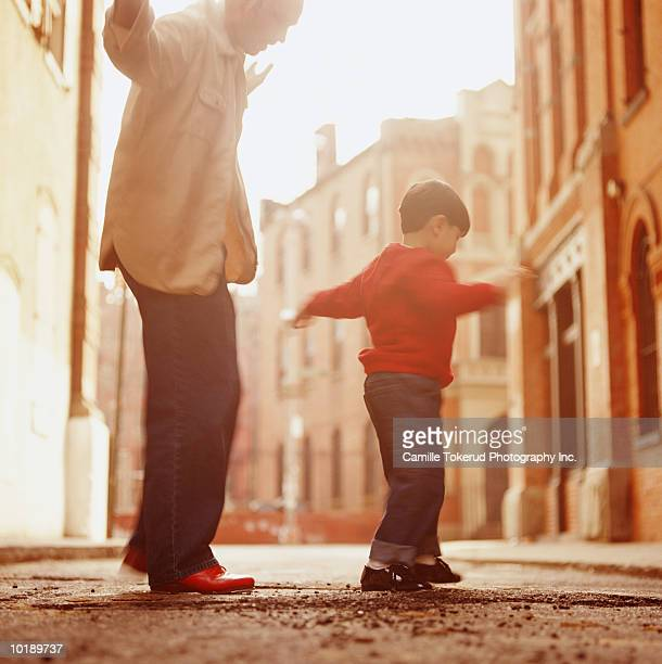 father and son (4-6 years) balancing on board on street - 6 7 years stock pictures, royalty-free photos & images