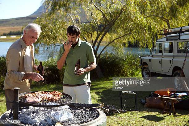 Father and son barbecuing at camp site