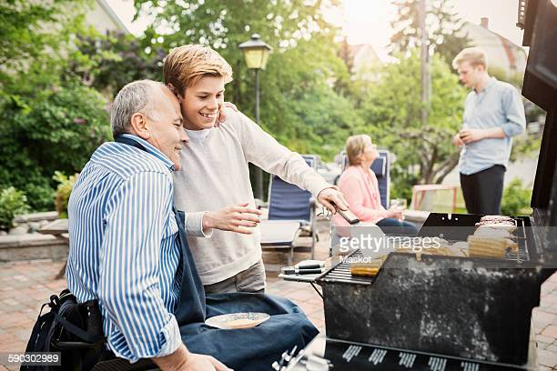father and son barbecuing at yard