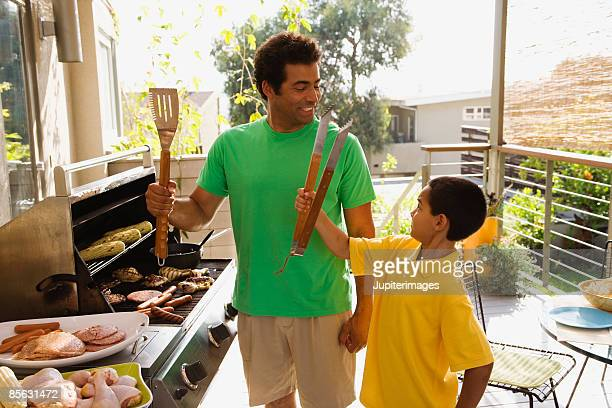 father and son barbecuing - funny bbq stock pictures, royalty-free photos & images
