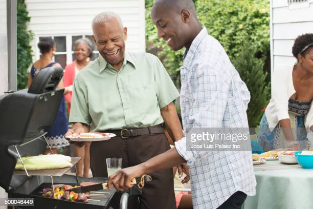 Father and son barbecuing together on patio