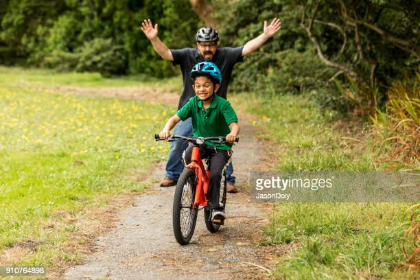 father and son bicycle riding - first occurrence stock pictures, royalty-free photos & images