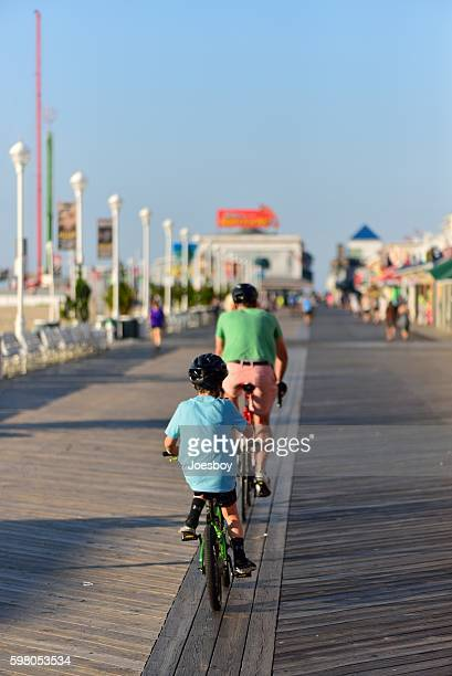 father  and son biking on boardwalk - ocean city maryland stock pictures, royalty-free photos & images