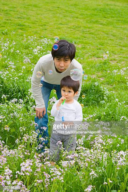 Father and son blowing bubbles in a meadow, Setagaya Ward, Tokyo Prefecture, Japan