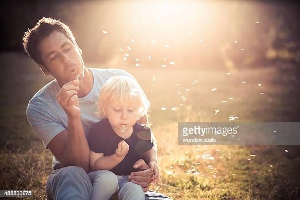 Father and son blowing dandelions