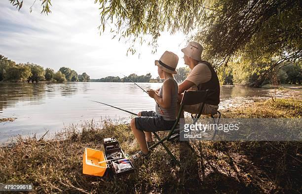 Vater und Sohn-Verschweißung beim Angeln Tag auf dem Fluss.
